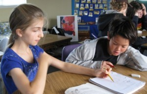 Mariah helps a fellow middle-school student understand a lesson at Living Wisdom School in Palo Alto, CA