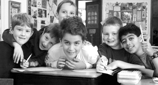 boys at living wisdom school leaning over desk laughing
