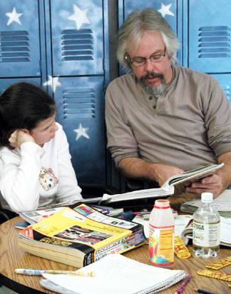 Gary McSweeney helps a middle school student with math at Living Wisdom School in Palo Alto, California.