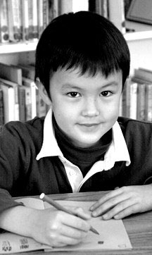 Boy seated at desk smiling with pen in hand, Living Wisdom School, Palo Alto, California