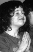 Young girl prays at Living Wisdom School