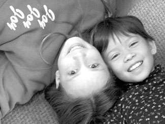 two girls lie on floor smiling