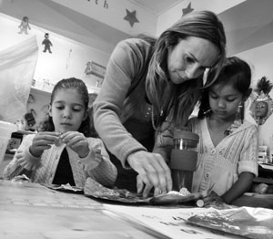 Living Wisdom School teacher Maria Jones helps her first-grade students with an art project.