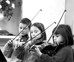 three young children playing violin