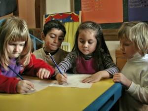 Kindergarten students work on writing at Living Wisdom School