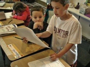 A boy reads from his writing at Living Wisdom School in Palo Alto, California
