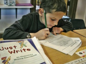 Young boy works on an assignment at Living Wisdom School
