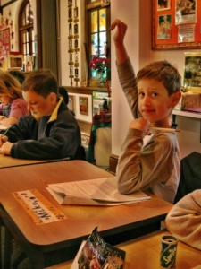 A boy raises his hand in class at Living Wisdom School in Palo Alto