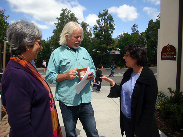 Teachers Helen, Gary, and Ruth confer during recess at Living Wisdom School in Palo Alto, California.