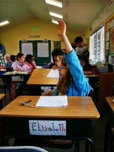 A student raises her hand for help in math class at Living Wisdom School in Palo Alto.