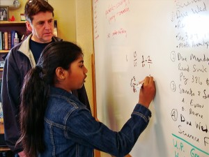 Eric watches as a student demonstrates her grasp of a problem-solving approach, at Living Wisdom School in Palo Alto.