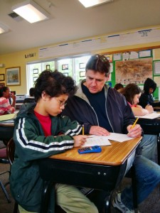Teacher Eric helps Luke understand a math concept at Living Wisdom School in Palo Alto, California.
