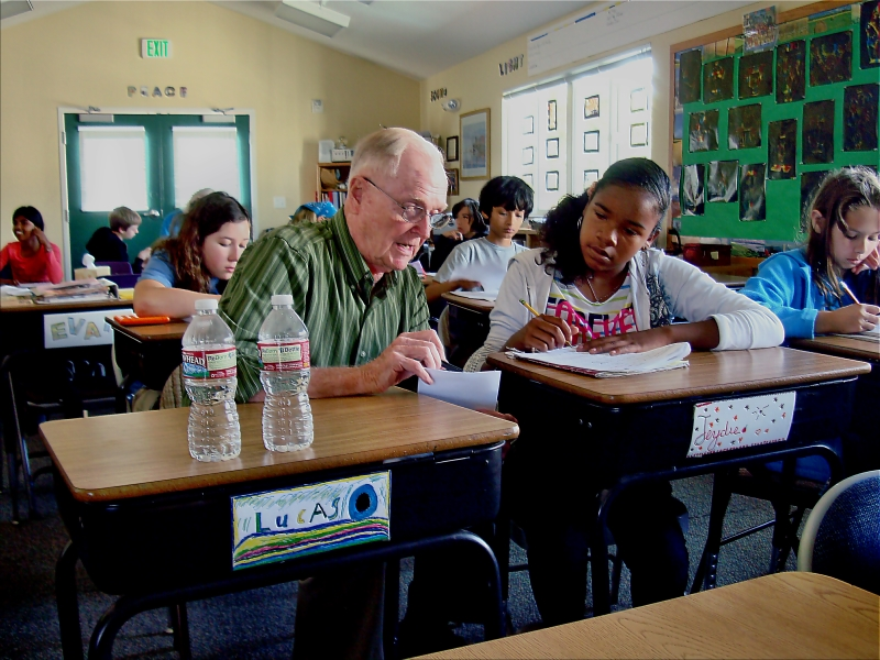 Volunteer math teacher Richard Fouquet helps a student at Living Wisdom School in Palo Alto, California.
