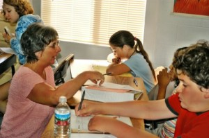 Photo: School director Helen helps a student in language arts. Individual attention is a constant, defining feature of academics at Living Wisdom School.