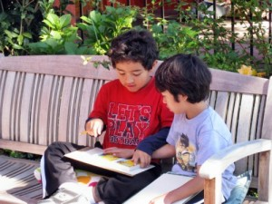Photo: Two boys help each other with homework. Few adults educated in traditional schools remember their learning years as fun. At LWS, many factors contribute to awaken the children's love of learning. As a result, scenes like this are common.